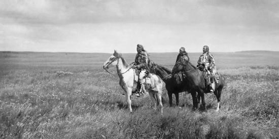 Tres jefes Pies negros a caballo en una pradera