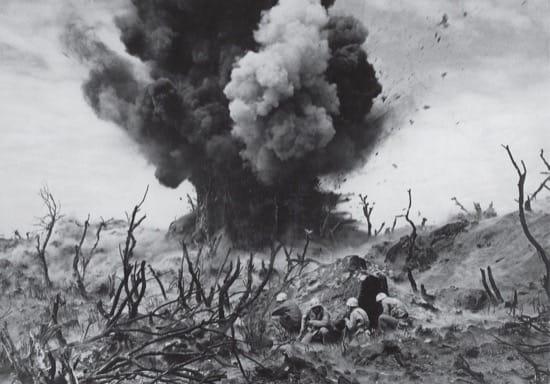 Marines cubriéndose durante la batalla de Iwo Jima mientras un búnker japonés es destrozado. Marzo 1945.