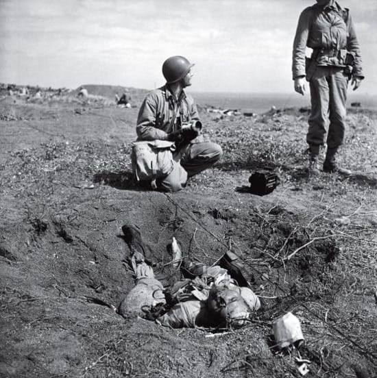 200 soldados japoneses fueron capturados tras la batalla de Iwo Jima. 20.000 murieron. Una muestra de que lucharon hasta la muerte. En la foto, no publicada en LIFE, dos soldados hablan junto al cadáver de un soldado japonés